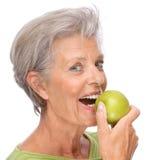 Senior woman with apple royalty free stock photo