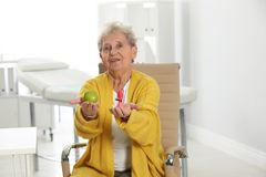 Senior woman with between apple and candy in hospital royalty free stock images