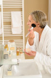 Senior woman apply make-up powder in bathroom royalty free stock images