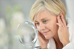 Senior woman applying anti-aging cream stock photography