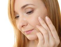 Senior woman applying anti-aging cream on face. Closeup Royalty Free Stock Image