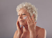 Senior woman applying anti-aging cream on her face Royalty Free Stock Photos