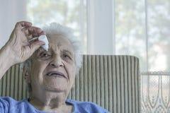 Senior woman applying  eye drop on her eye Royalty Free Stock Photo