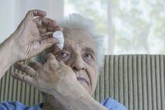 Senior woman applying  eye drop on her eye Royalty Free Stock Photos
