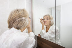 Senior woman applying eyeliner while looking at mirror in bathroom Royalty Free Stock Image