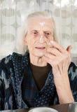 Senior woman applying face cream Royalty Free Stock Photography