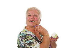 Senior woman applying lotion on her face Stock Photography