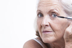 Senior woman applying mascara Stock Image