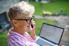Senior woman architect with smartphone working outdoors in garden, home office concept.