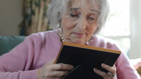 Senior Woman In Armchair At Home Looking At Photo Album stock video
