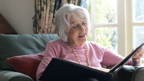 Senior Woman In Armchair At Home Looking At Photo Album stock footage