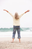 Senior Woman With Arms Outstretched On Beach royalty free stock images