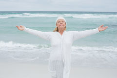 Senior woman with arms outstretched at beach Stock Photo