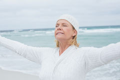 Senior woman with arms outstretched at beach Stock Images