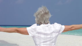 Senior Woman With Arms Outstretched On Beautiful Beach stock video