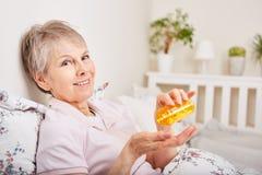 Senior as patient takes medication. Senior woman as sick patient takes medication Royalty Free Stock Photography
