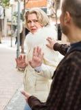 Senior woman asking man. Senior women asking men not to bother her outdoor Royalty Free Stock Photos
