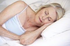 Senior Woman Asleep In Bed Stock Image