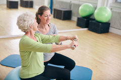 Senior woman assisted by personal trainer in gym Royalty Free Stock Photography