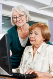 Senior Woman Assisting Friend In Computer Class Stock Photo