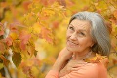 Senior woman in  autumn park Stock Photos
