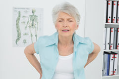 Senior woman with back pain in medical office Stock Photo