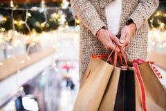 Senior woman with bags doing Christmas shopping. Unrecognizable senior woman with paper bags doing Christmas shopping. Shopping center at Christmas time Royalty Free Stock Image