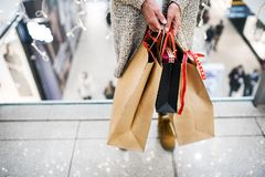 Senior woman with bags doing Christmas shopping. Unrecognizable senior woman with paper bags doing Christmas shopping. Shopping center at Christmas time royalty free stock photography