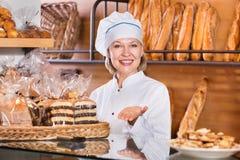 Senior woman at bakery display Stock Photos