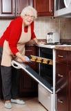 Senior woman baking cookies. Happy senior woman baking cookies Royalty Free Stock Photography