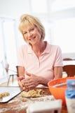 Senior Woman Baking Cookies In Kitchen Stock Photography