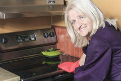 Senior woman baking cookies on the stove Royalty Free Stock Images