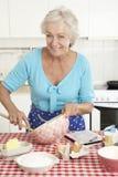 Senior Woman Baking In Kitchen Stock Image