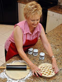 Senior woman baking pie. An older woman making a fruit pie crust at home in her kitchen stock images
