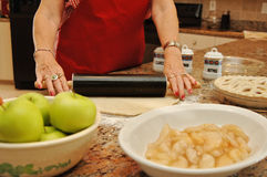 Senior woman baking pie. Hands of an older woman making a apple pie at home in her kitchen Stock Photos
