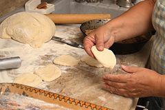 Senior woman baking pies in her home kitchen.Grandma cooks pies. Home cooked food. omemade mold cakes of the dough in. The women`s hands. The process of making Stock Photo