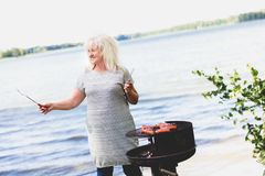 Senior woman barbecuing by the lake. Royalty Free Stock Images