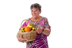 Senior woman with basket of fruit. Senior woman presenting a basket full of fresh fruit Royalty Free Stock Photography