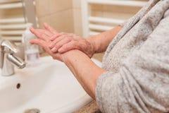 Senior woman in bathrobe applying hand cream in bathroom, closeup stock image