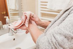 Senior woman wipes her hands with a towel in bathroom in morning time, closeup royalty free stock photos