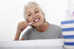 Senior Woman In Bathroom Brushing Teeth Royalty Free Stock Image