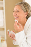 Senior woman in bathroom use cotton pad stock image