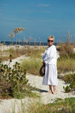 Senior woman on beach. Smiling senior aged woman stood barefoot on beach. summer scene stock images