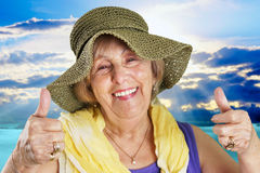 Senior woman at the beach. Happy senior woman at the beach two thumbs up Royalty Free Stock Photos