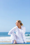 Senior woman beach yoga Stock Images