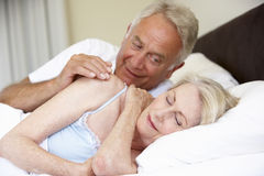 Senior Woman In Bed With Amorous  Husband Stock Photo