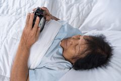 senior woman in bed pressing snooze button on morning alarm clock stock image