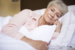 Senior woman in bed Stock Image