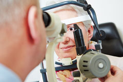 Senior woman behind slit lamp at Royalty Free Stock Photo