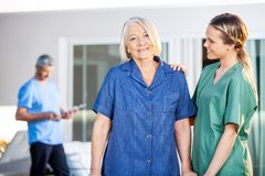 Senior Woman Being Assisted By Female Caretaker In. Portrait of smiling senior women being assisted by female caretaker in nursing home stock images